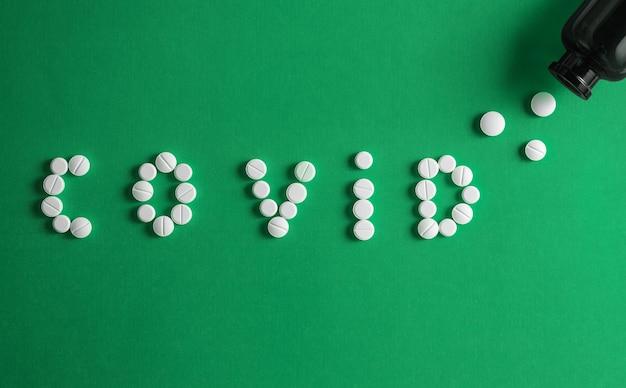Plat leggen van medicijnpillen vorm als woord covid 19, gezondheidszorgconcept en de verspreiding van pandemie covid-19, coronavirus voorkomen