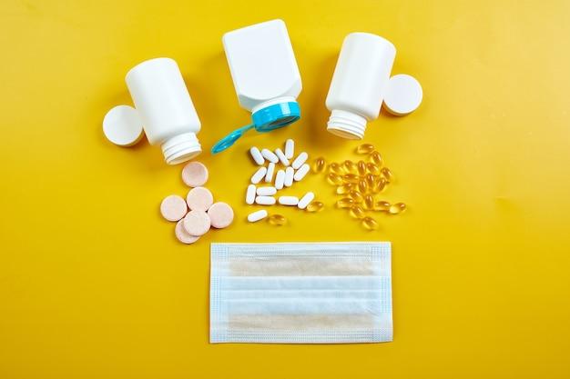 Plat leggen van medische gezichtsmasker en pillen, visolie, vitamines op geel
