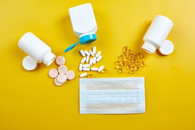 Plat leggen van medische gezichtsmasker en pillen visolie vitamines op gele achtergrond coronavirus