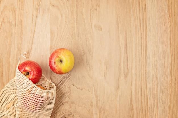 Plat leggen van milieuvriendelijke herbruikbare katoenen netzak met appels. duurzaam, ethisch, plasticvrij levensstijlconcept zonder afval. bovenaanzicht