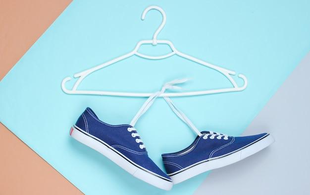 Plat leggen van moderne blauwe sneakers schoenen met hanger op pastel achtergrond.