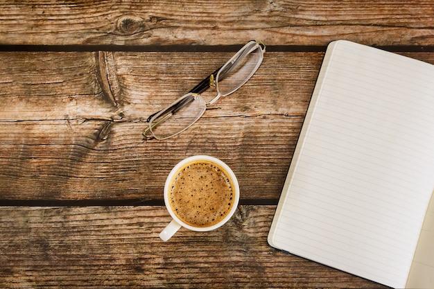 Plat leggen van moderne kantoor tafel met lege notebook pagina in koffiekopje op houten rustieke tafel