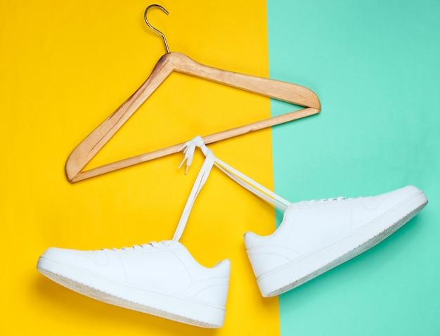 Plat leggen van moderne witte sneakers schoenen met hanger op pastel achtergrond.