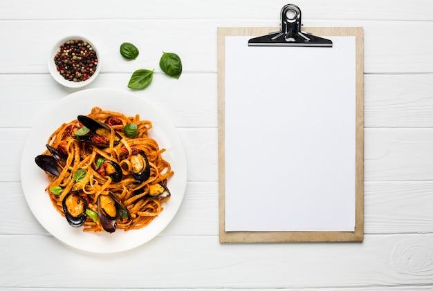 Plat leggen van mosselen pasta met klembord