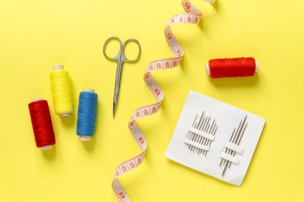 Plat leggen van naai-accessoires. draden, naalden, centimeter en schaar op geel oppervlak, bovenaanzicht.