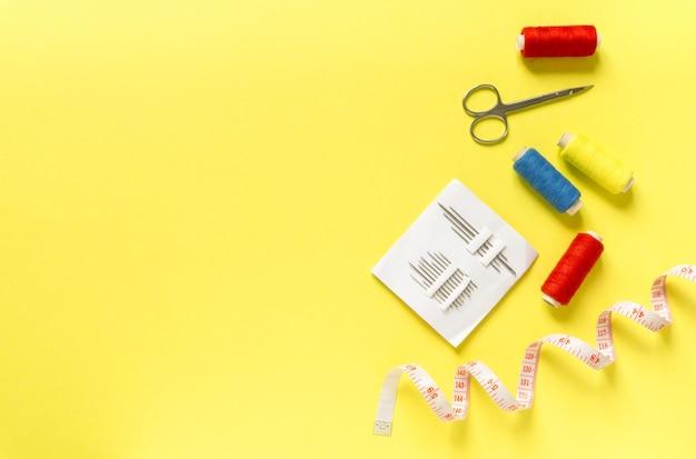 Plat leggen van naai-accessoires. draden, naalden, centimeter en schaar op geel oppervlak, ruimte voor tekst.