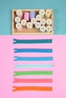 Plat leggen van naaigarnituur bevat de ritssluiting en kleurrijke draadrollen om te naaien.