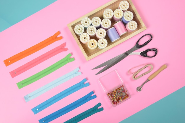 Plat leggen van naaigarnituur bevat de stoffen, schaar, rits en draadrollen.