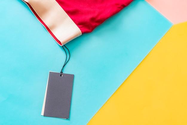 Plat leggen van nieuwe mannelijke rode ondergoedbroek geïsoleerd met leeg prijskaartje op creatieve kleurenachtergrond f