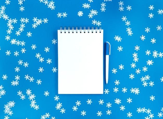 Plat leggen van notebook en een pen op blauw