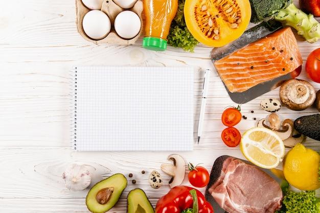 Plat leggen van notebook met ingrediënten en zalm