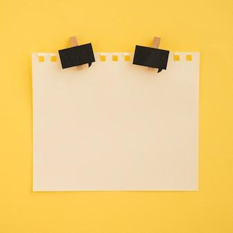 Plat leggen van notitie en paperclips met gele achtergrond