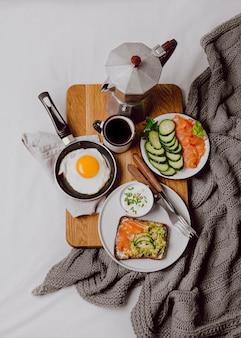 Plat leggen van ontbijtsandwiches op bed met gebakken ei en toast