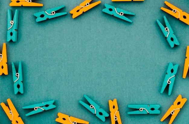 Plat leggen van oranje en turquoise kleding pins frame