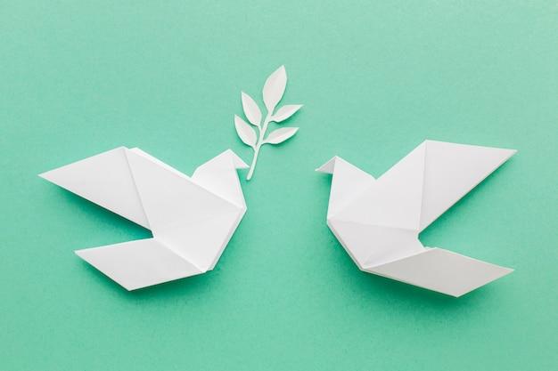 Plat leggen van papieren duiven met bladeren