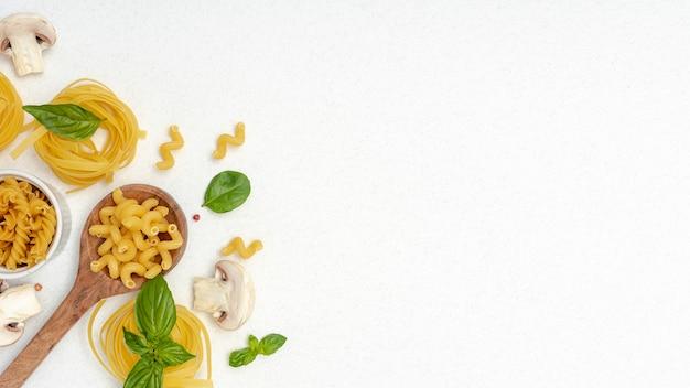 Plat leggen van pasta en houten lepel op effen achtergrond met kopie ruimte