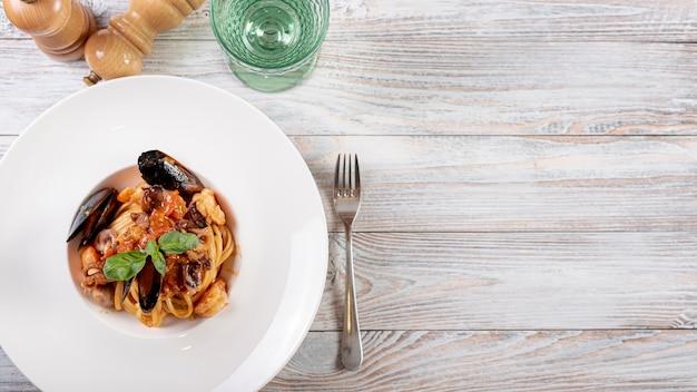 Plat leggen van pasta en schelpen op houten tafel