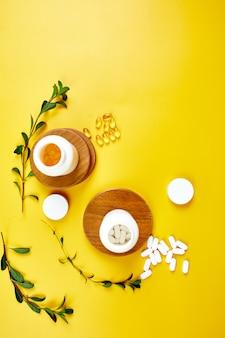 Plat leggen van pillen, visolie, vitamines met groene bladeren op geel