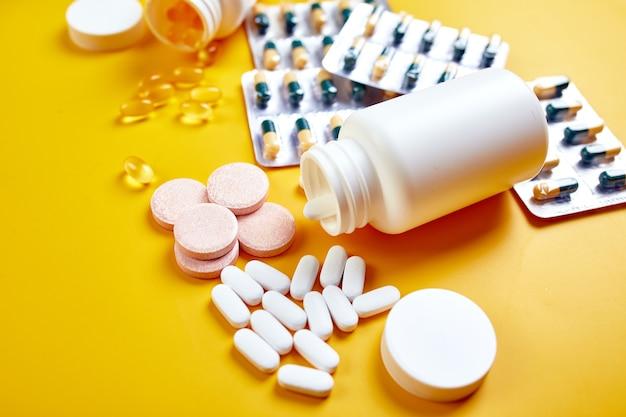 Plat leggen van pillen, visolie, vitamines op geel