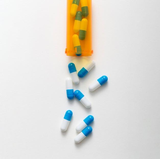 Plat leggen van plastic container met pillen die eruit komen