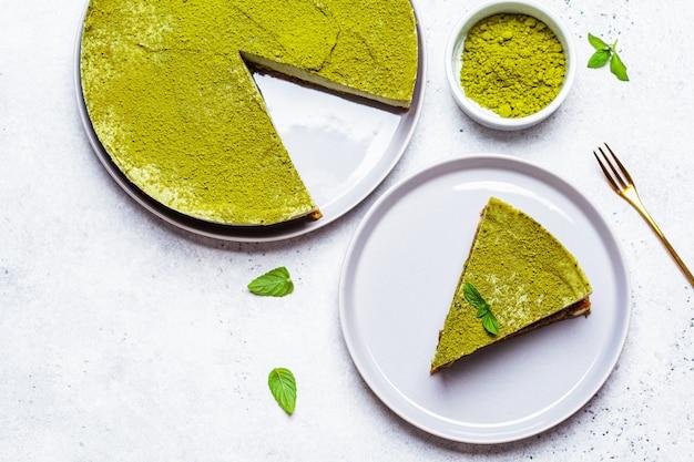 Plat leggen van rauwe vegan matcha cheesecake, witte achtergrond