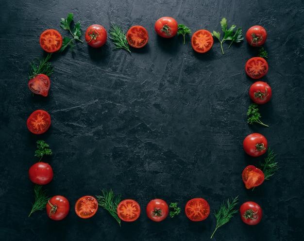 Plat leggen van rode rijpe tomaten ligt in de vorm van een frame op een donkere achtergrond met groene peterselie en dille.