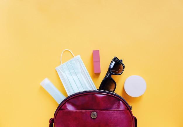 Plat leggen van rood lederen vrouwentas open met cosmetica, accessoires en masker met alcoholgel ontsmettingsmiddel op geel