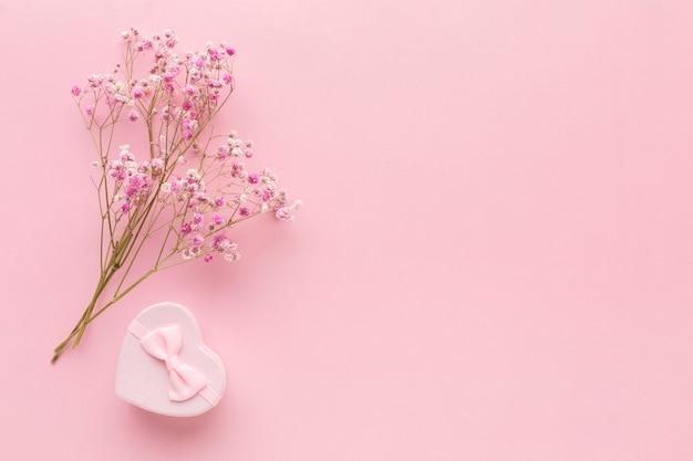 Plat leggen van roze geschenk met bloemen en kopie ruimte