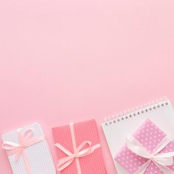 Plat leggen van roze geschenken met laptop- en kopie ruimte