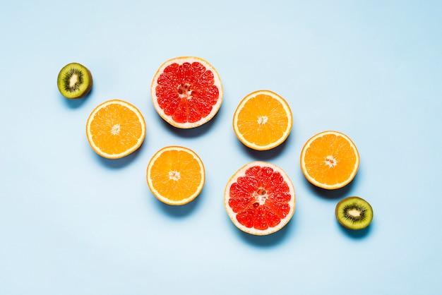 Plat leggen van sappige sinaasappelen, grapefruits en kiwi's