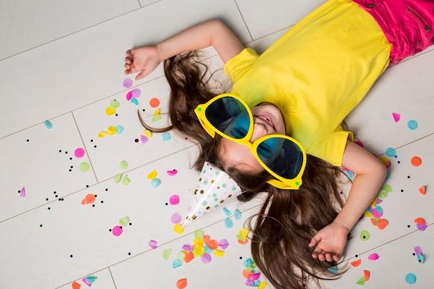 Plat leggen van schattig klein meisje met grote zonnebril