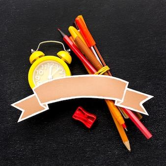 Plat leggen van schoolbenodigdheden met klok en potloden