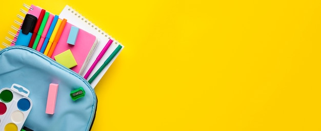 Plat leggen van schoolbenodigdheden met potloden in rugzak en kopieerruimte