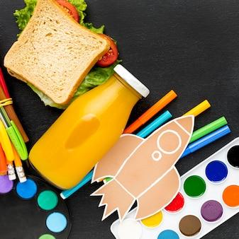 Plat leggen van schoolbenodigdheden met sandwich en potloden
