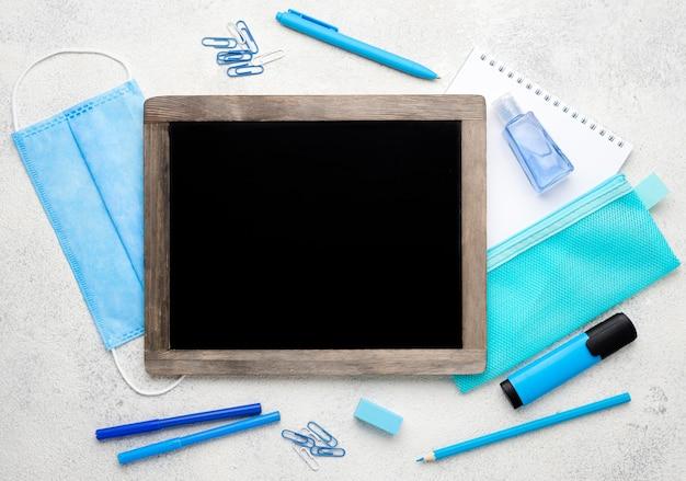Plat leggen van schoolbenodigdheden met schoolbord en medisch masker