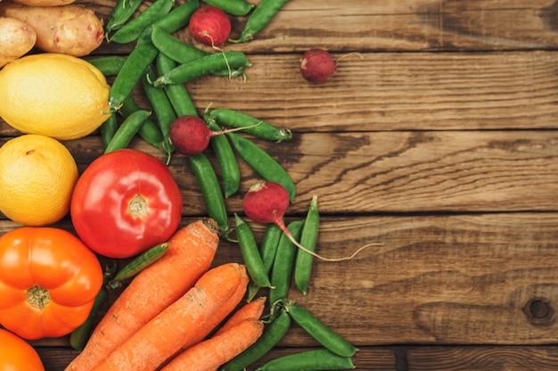 Plat leggen van seizoensfruit, groenten en kruiden. zomer voedselconcept. gezond leven en vegetarisch, veganistisch, dieet, schone voedselingrediënten. plaats voor tekst. voedsel op een donkere houten achtergrond.