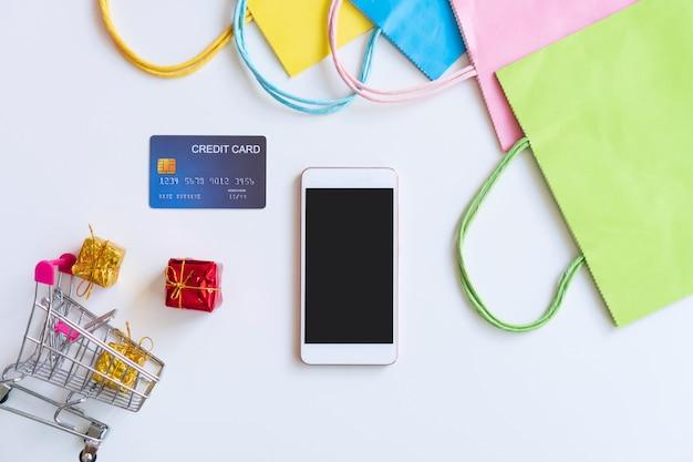 Plat leggen van smartphone, creditcard, miniatuur geschenkdozen. trolley en kleurrijke tassen op witte tafel. bovenaanzicht en kopieer ruimte voor tekst. online winkelen, nieuw normaal, technologie en lifestyle concept.
