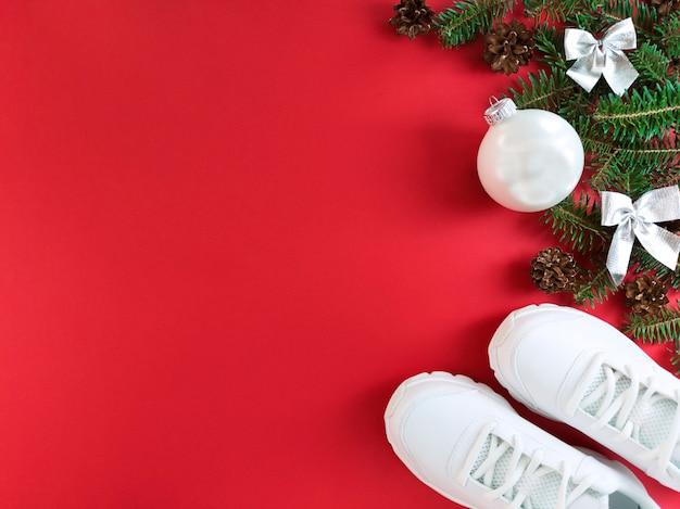 Plat leggen van spar boomtakken, kegels, kerstbal en trainers op rood papier.