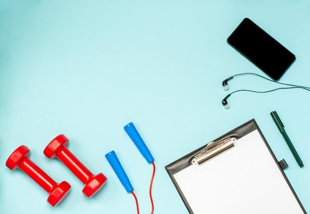 Plat leggen van sportartikelen voor fitness op een blauwe ondergrond
