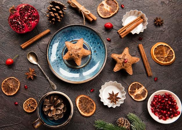 Plat leggen van stervormig koekje met dennenappels en granaatappel
