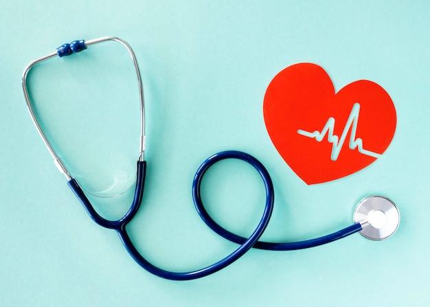Plat leggen van stethoscoop met hart van papier