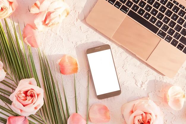 Plat leggen van stijlvolle compositie met laptop, mobiele telefoon. tropisch palmblad, roze roze bloemen, op pastel met schaduwen en zonlicht