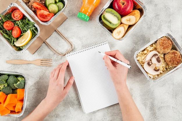 Plat leggen van stoofschotels met maaltijden en hand schrijven op laptop