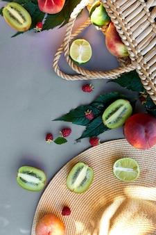 Plat leggen van strohoed en tas met fruit op grijze achtergrond in zonlicht, zomer