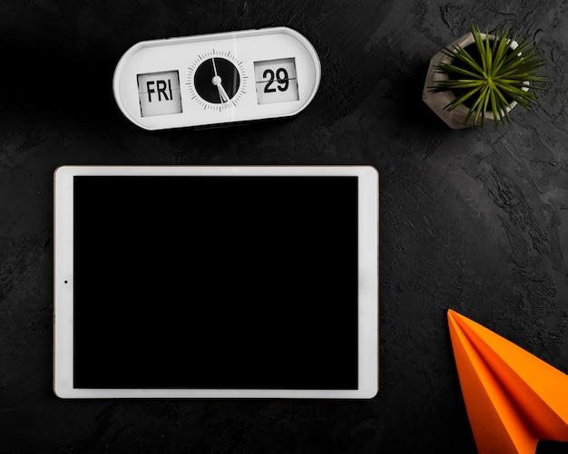 Plat leggen van tablet klok en papieren vliegtuigje