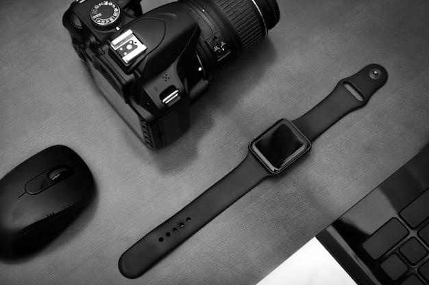 Plat leggen van techno items voor moderne werknemer met smartwatch mobiele telefoon en dslr camera op houten tafel.