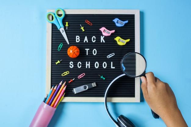 Plat leggen van terug naar school concept op blauwe achtergrond met de hand met een vergrootglas