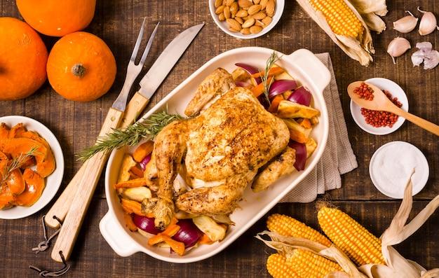 Plat leggen van thanksgiving-tafel met maïs en geroosterde kip