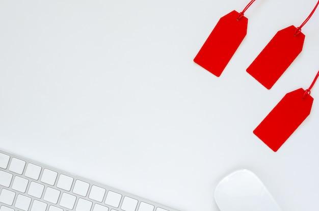 Plat leggen van toetsenbord en muis met rode prijskaartje op witte achtergrond voor cyber monday online verkoopconcept.