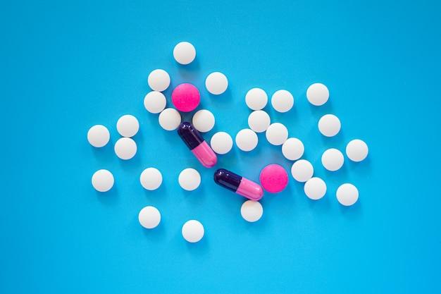 Plat leggen van veel pillen en tabletten op blauwe achtergrond